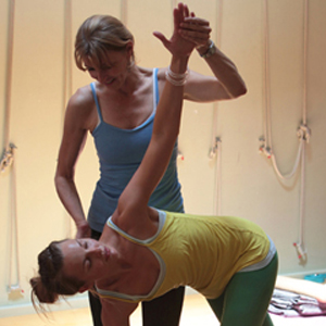 a yoga student with arm up and erika the instructor helping with the correct position
