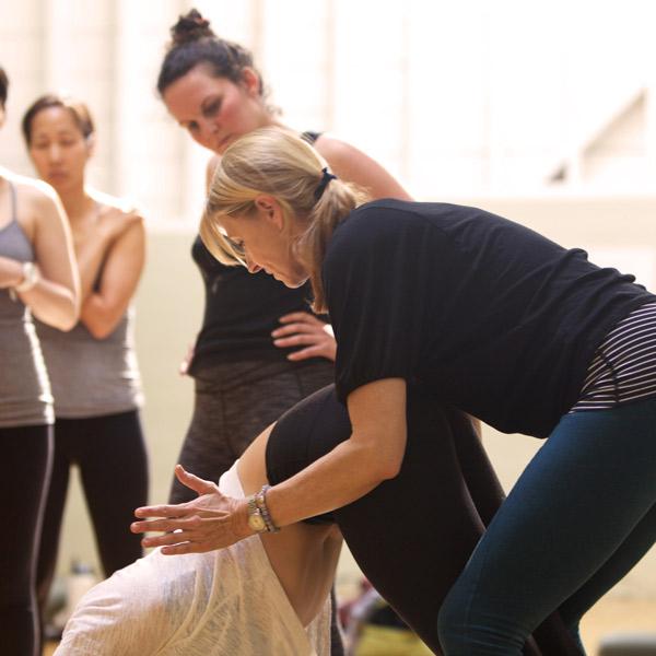 erika teaching other aspiring yoga teachers about yoga poses