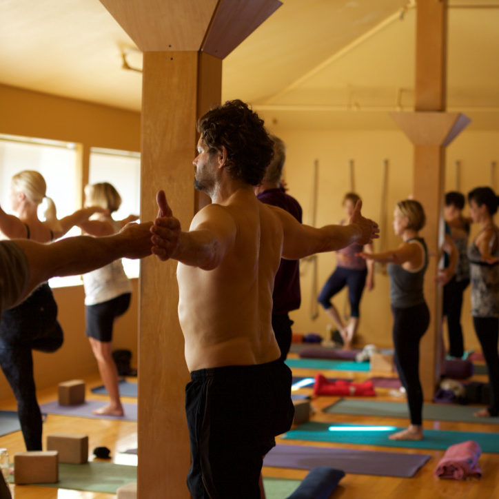 man and others holding arms out in a yoga class