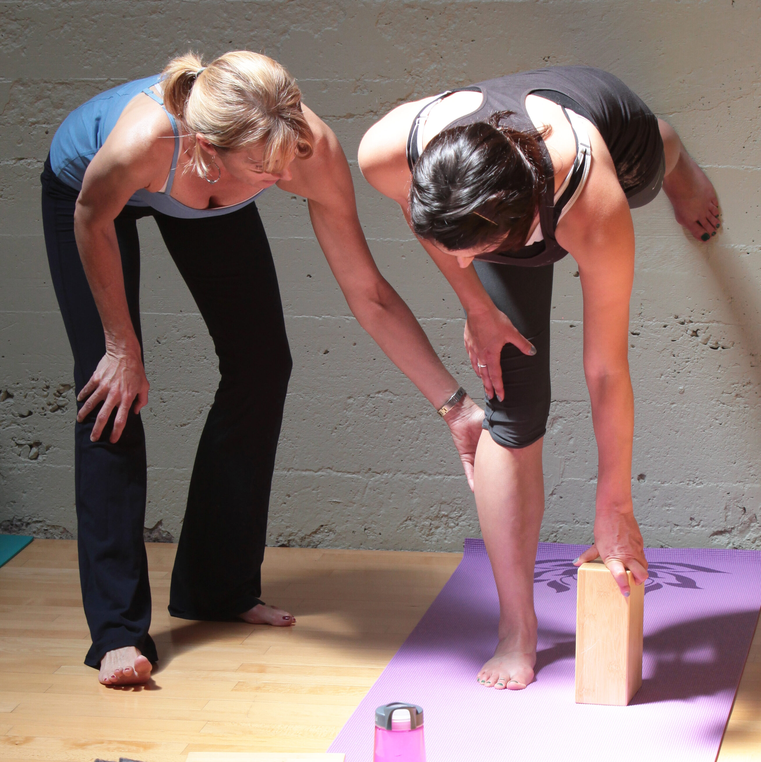 erika teaching a yoga student the correct position for a pose