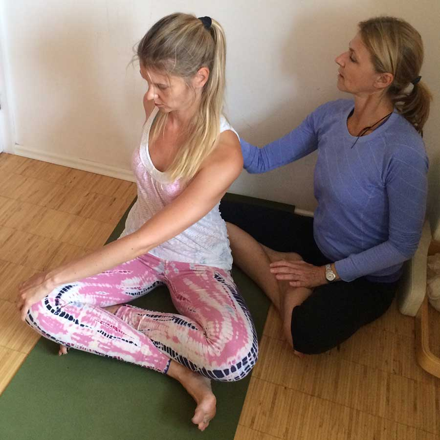 Erika with a student in yoga private instruction, sitting on floor