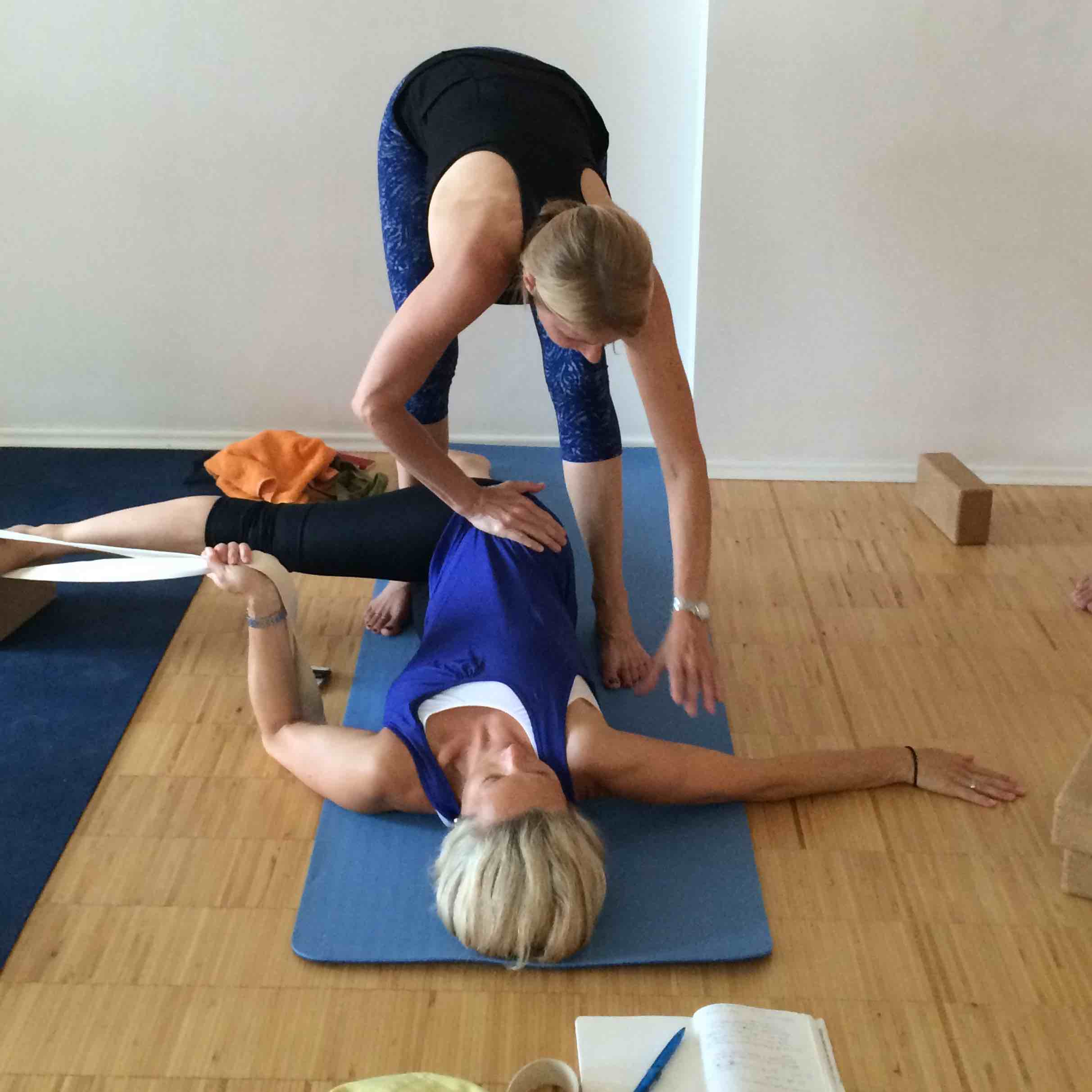 erika helping yoga student in a laying down pose